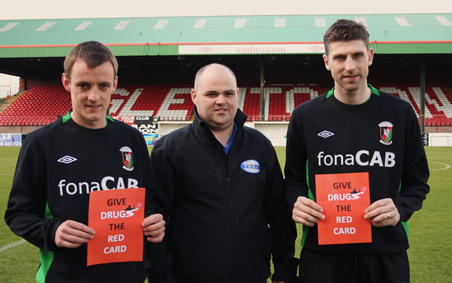 Glentoran's Jason Hill and Paul Leeman help James Scott from FASA (centre) launch the FASA 'Give Drugs the Red Card' Day at the Oval on Saturday 30th April 2011