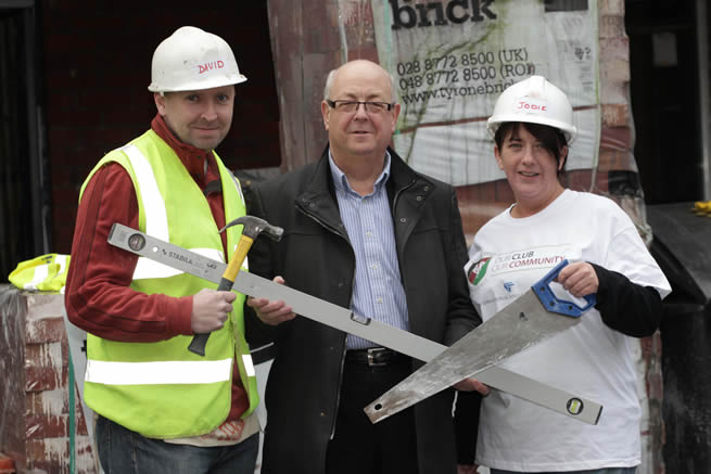Volunteers at the Glentoran Community Build Day Rev. David Thompson (left) and Jodie Killops (right) demonstrate to Aubry Ralph, Chairman of Glentoran the work they have been doing to help Habitat for Humanity NI build homes on Templemore Avenue for families in East Belfast.