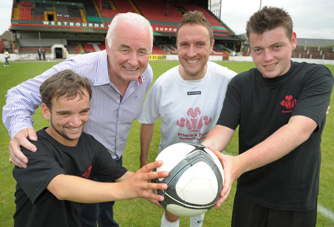 Young People Stephen Watson (left) and Christopher Haliday (right) demonstrate their football coaching skills to Chris Lyttle MLA (inside right) and Terence Brannigan, Chairman of Glentoran and board member of The Prince's Trust (inside left) after participating in The Prince's Trust 'Get Started with Football' programme